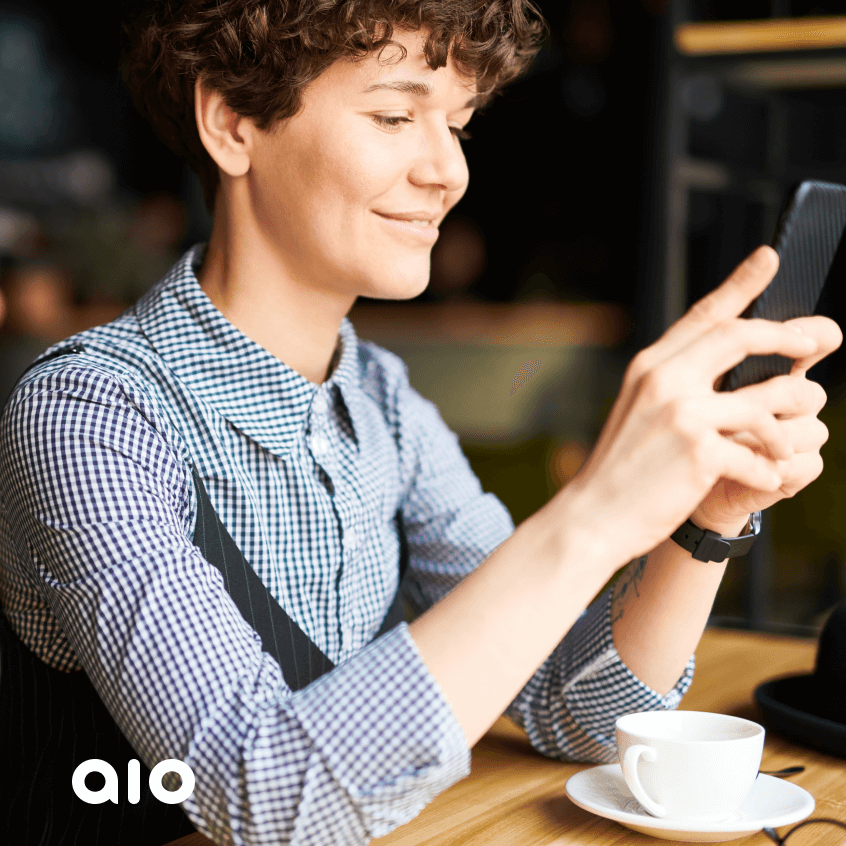 A woman in a shirt, sitting at the desk, dinking coffee, and checking her phone.