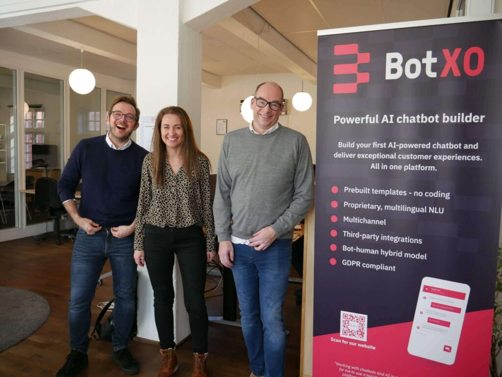 Three people standing in the office and smiling, with a Chatbot poster on the right side
