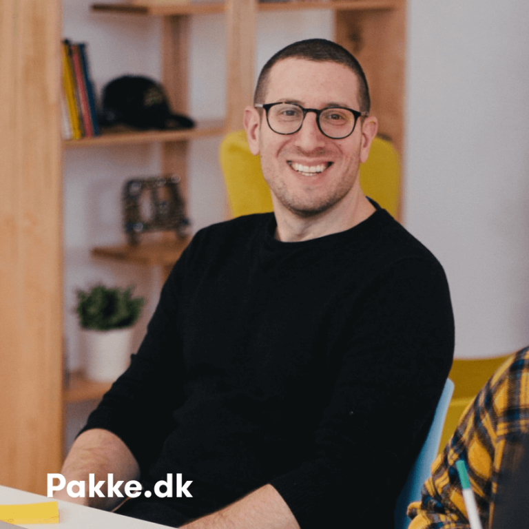 Image of smiling man in black top looking at camera, with pakke.dk text on bottom left corner.