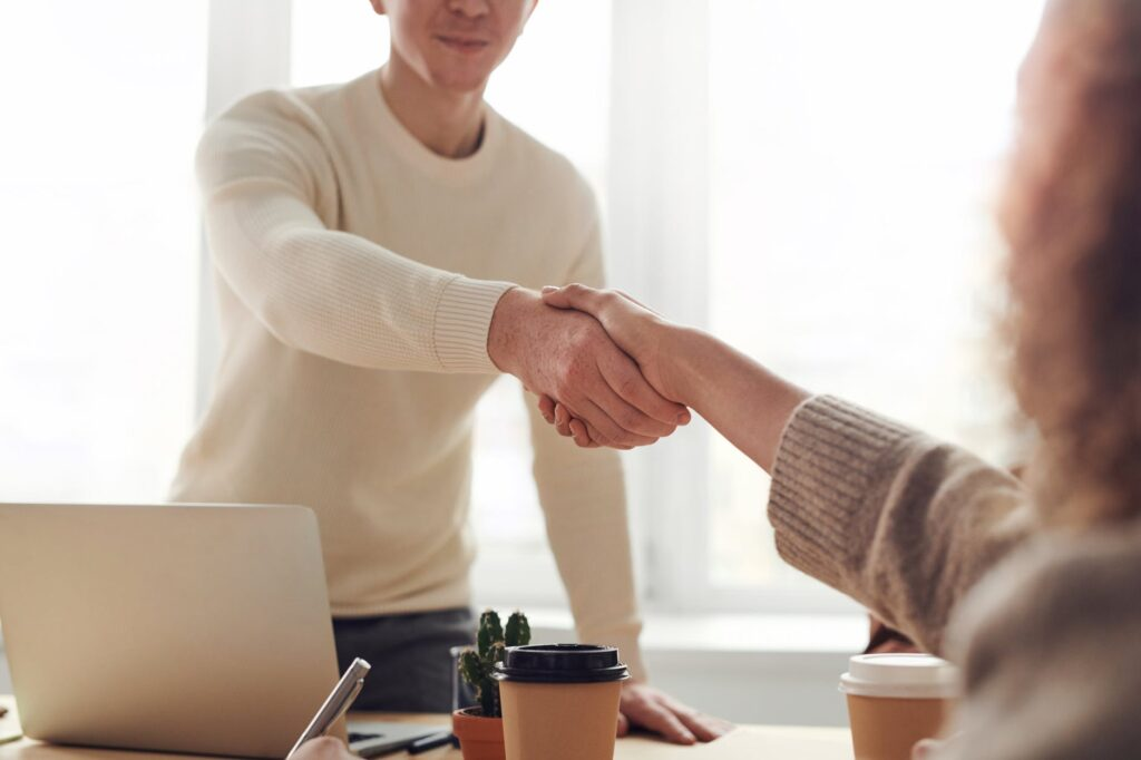 Two people shaking hands over the office desk.