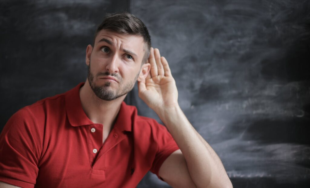 An image of a man in a red shirt actively listening.