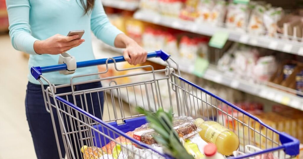 Woman looks at her smartphone whilst pushing a trolley full of groceries in a supermarket