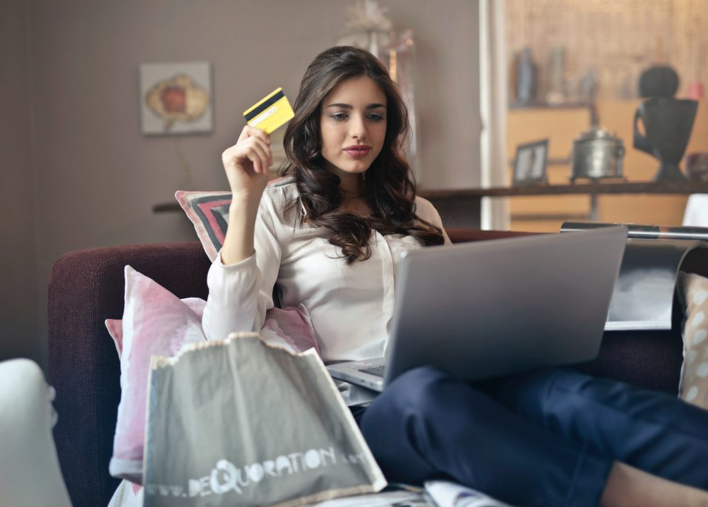 woman sitting on sofa holding a credit card looking at the screen of a laptop
